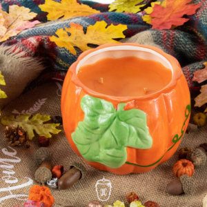 pumpkin candle with green leaf in a setting of autumn leaves