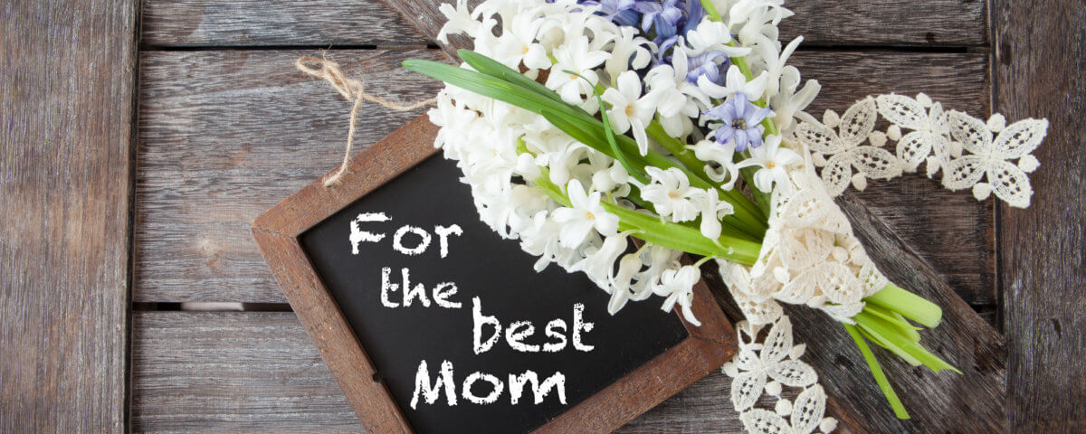Happy Mother's Day written on a chalk board Little bunch of white and blue hyacinths on rustic wooden background