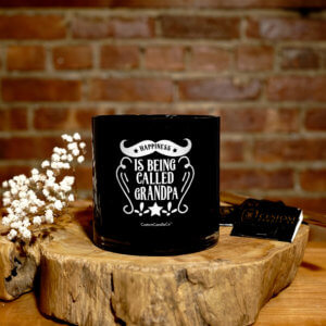 Black tumbler with silver top with a quote that says Happiness is being called Grandpa on a wooden background