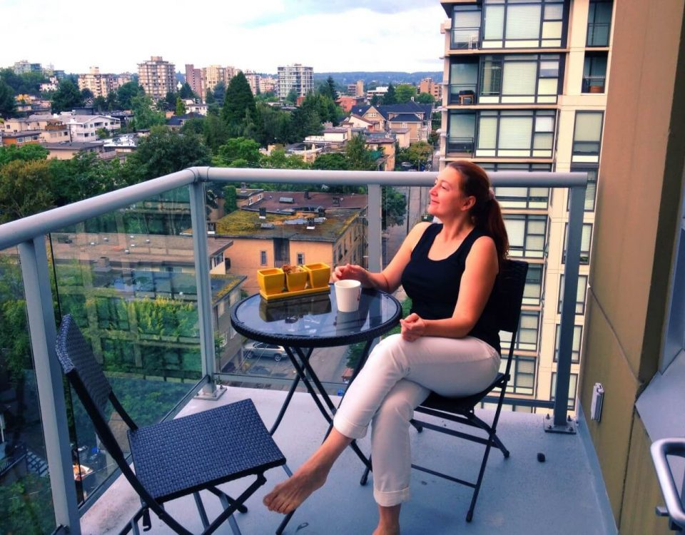 Woman enjoying morning coffee on a balcony of a high rise overlooking the city outdoor